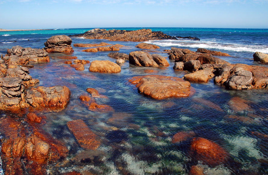 Bronze-red rock, crystal clear water, turquoise and ultramarine sea, cerulean sky stretching away and away Fergus Murray