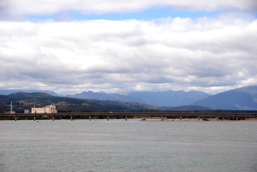 The wide Hokitika River and Weestland Dairy plant with mountain backdrop and low sky from the harbour spit.