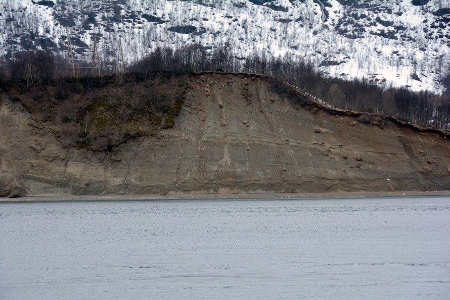 An ice-front delta  near Jøvik on the Ullsfjorden deposited during the Younger Dryas glaciations when the sea level was 65m higher than today. The glacier nose was to the left and the delta was deposited by a meltwater stream. NB telegraph poles for scale