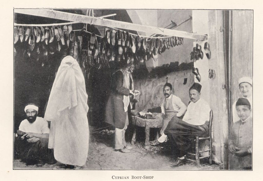 Turkish men and children and one veiled woman gathered about a boot shopUnknown Cyprian Boot-Shop (1900). From Travelers in the Middle East Archive (TIMEA). http://hdl.handle.net/1911/10019