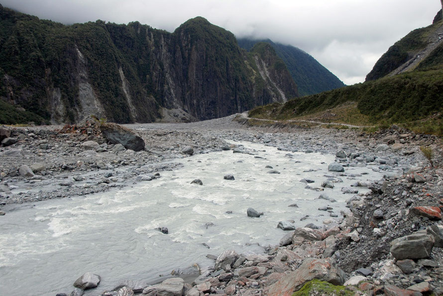 The cloudy waters of the glacier fed stream in the Fox Glacier valley and rock- and tree-fall scars on Cone Rock.