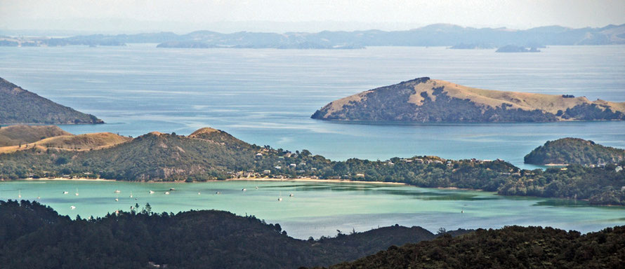 The turquoise, placid sea at Coromandel Harbour with the Ruffin Peninsula and Waimate Island with the distant islands of the Hauruki Gulf - Waiheke, Ponui and the mainland Hunua Ranges.