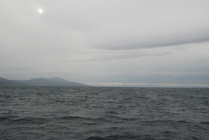 A weak sun over Stewart Island from the Foveaux Strait.
