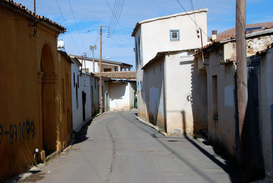Street in Peristerona with houses on left with walled yards