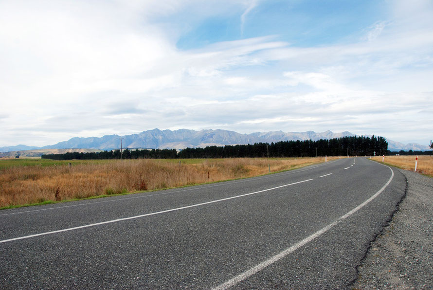 The road racing away to the ever-closer mountains on the dead flat valley bottom of the Waiau river before Manapouri.