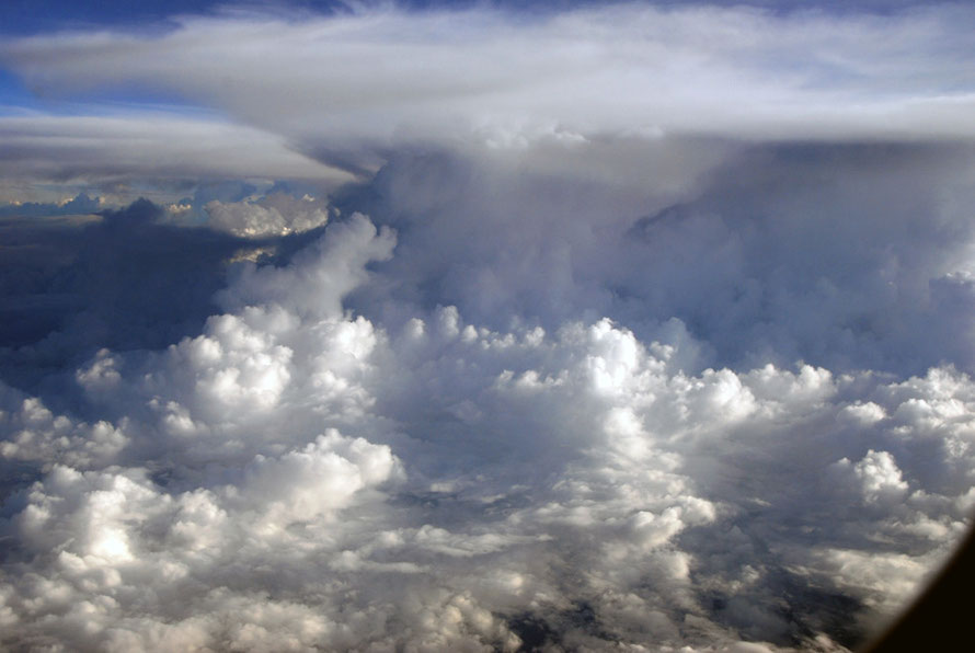 Staggering cloud formations and hefty turbulence towering over our plane flying at 36,000 feet above the 4884 m high mountains of Papua New Guinea on the return journey