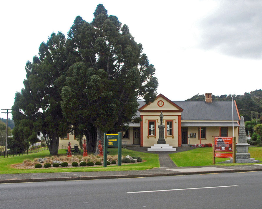 Coromandel Town Hall with Maori carvings, war memorial and Kauri trees.