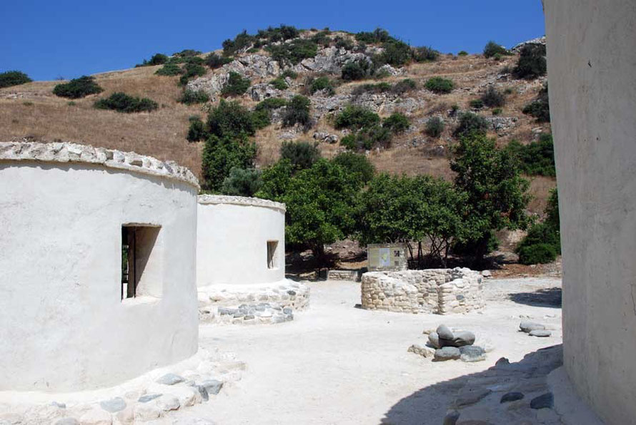 Reconstructed round houses showing steep knoll behind which is site of ruined village, Khirokitia