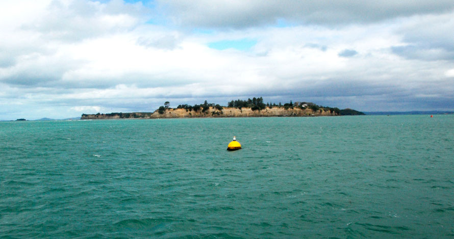 Yellow channel marker buoy and the planed off southern end of Te-Motu-a-Ihenga/Motuihe Island in the Hauraki Gulf.