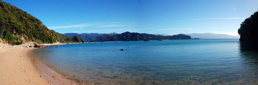 Panoramic view of Wainui Bay from near Taupo Point with Abel Tasman Point and the distant Wakamarama mountains to the west.
