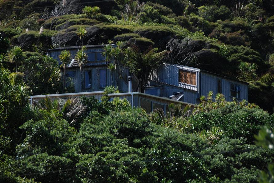 Upscale bach built into the hillside above Karakere Beach.
