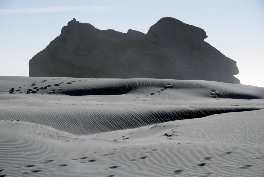 Wind blown sand and massive rock formations at Wharariki Beach west of Golden Bay.