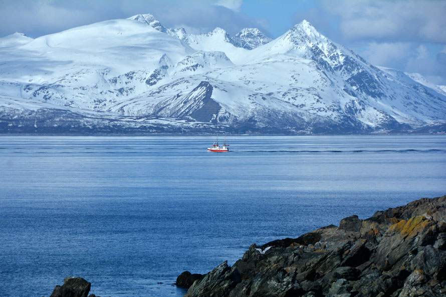 A fishing boat against the mountains of Vanntinden Island seen from Russelv at the end of the Lyngen Peninsula, Northern Norway, April 2015.