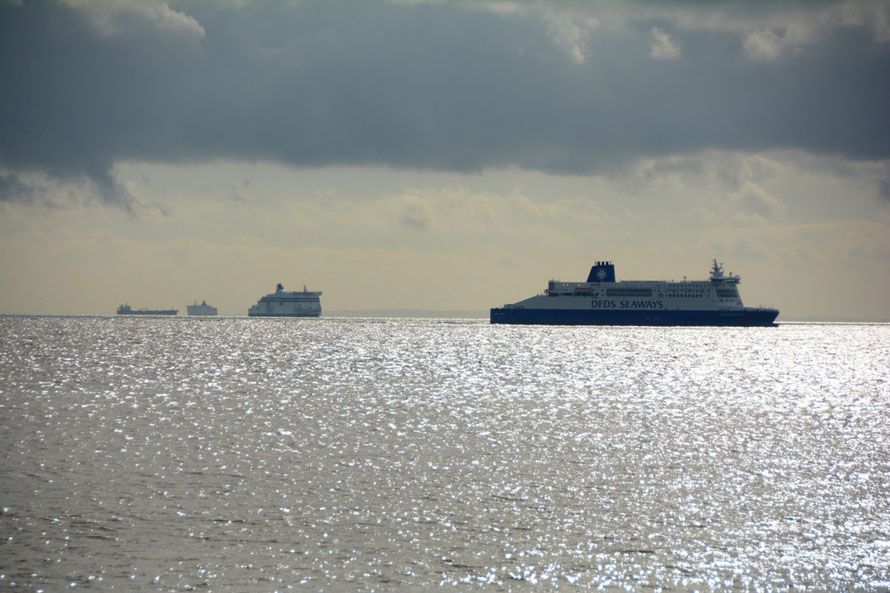 An array of ferries and shipping with the French coast in the background.