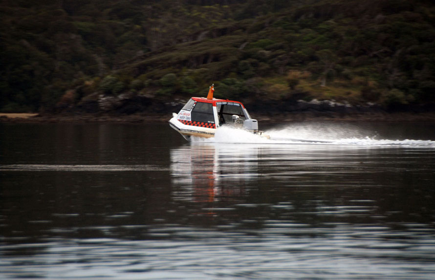 The first water taxi of the moring heads out to Ulva across the glassy waters of Paterson Inlet.
