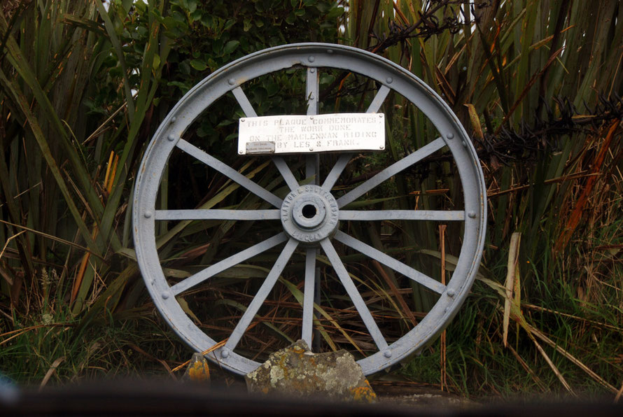 Between Clutha and Tautuka on a steel tractor wheel: 'This plaque commemorates the work done on the Maclennan Riding by Les and Frank: Les Dewe Frank Chalmers'.