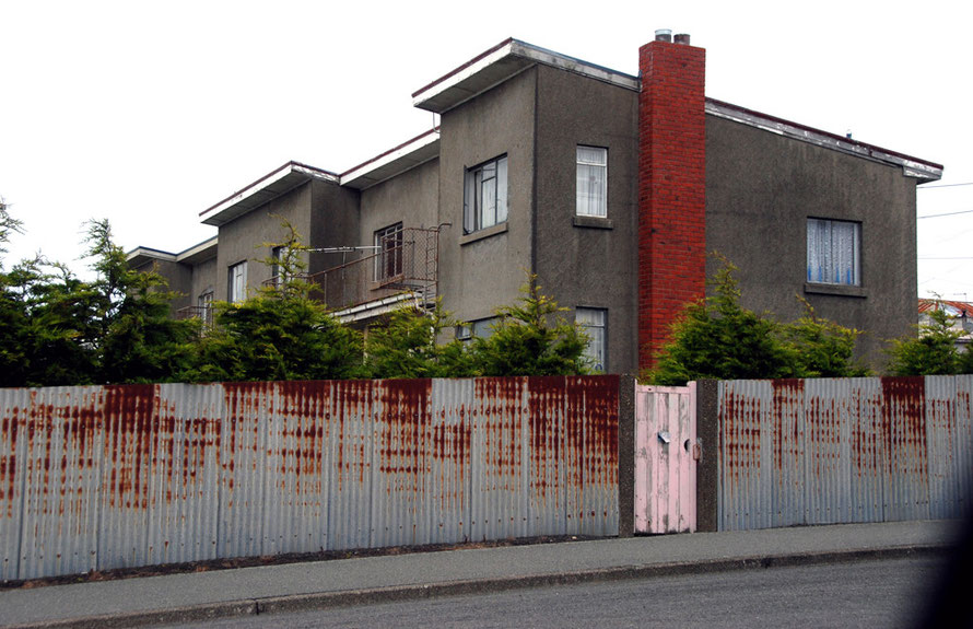 Pebbledashed low-rise apartments, corrugated iron fence and pink gate, East End, Bluff, Southland, NZ.