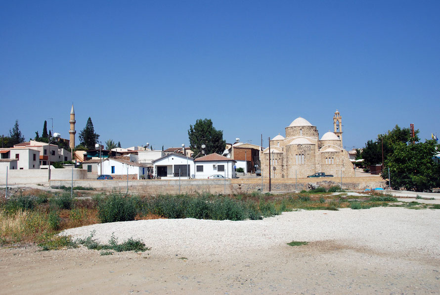 The Church of St Barnabas and Hilarion and the Peristerona Mosque from the eastern bank of the bone dry Peristerona river in searing heat in late June 2012
