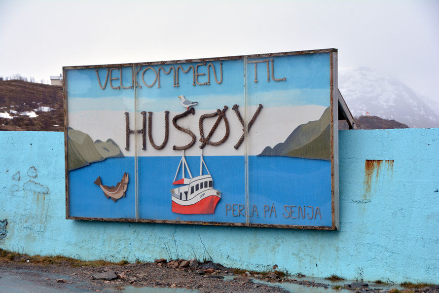 'Welcome to Husøy' on Senja Island. Husøy with its snow, sleet, steep road, tunnel and drying fish heads with hooded crows perched above them seemed like the inhospitable end of the world after driving too many miles in foul weather.