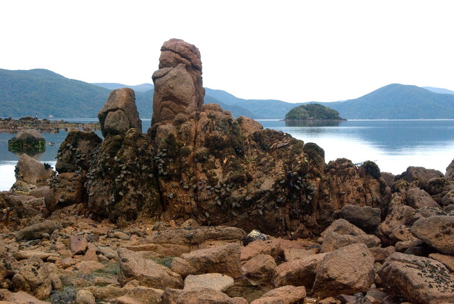 Stewart Island is made up of intrusive granite, much of which is weathered and rotten - these formations are on Boulder Beach, Ulva with Tamihau Island and the rounded hills of the 'mainland' in the b