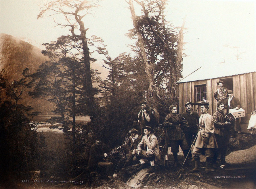 A mixed group of Victorian hikers/trampers prepares to strike out on the Milford Track from this hut at the head of Lake Te Anau. It looks as if four of the party are guides or porters. (Burton Bros, 1895 Turnbull C