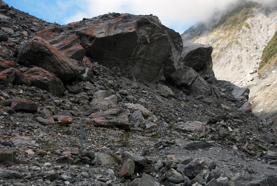 More huge boulders and roche moutonnée ('sheepback')  left by an earlier passages of the Fox Glacier. Ice thaw and melt allow the glacier to pluck the down-glacier side of the moutonée away.