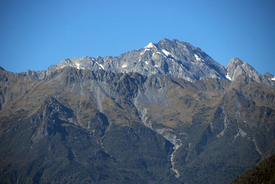 The rocky snow free peak of Mt Fletcher in the Southern Alps with Butler range in foreground