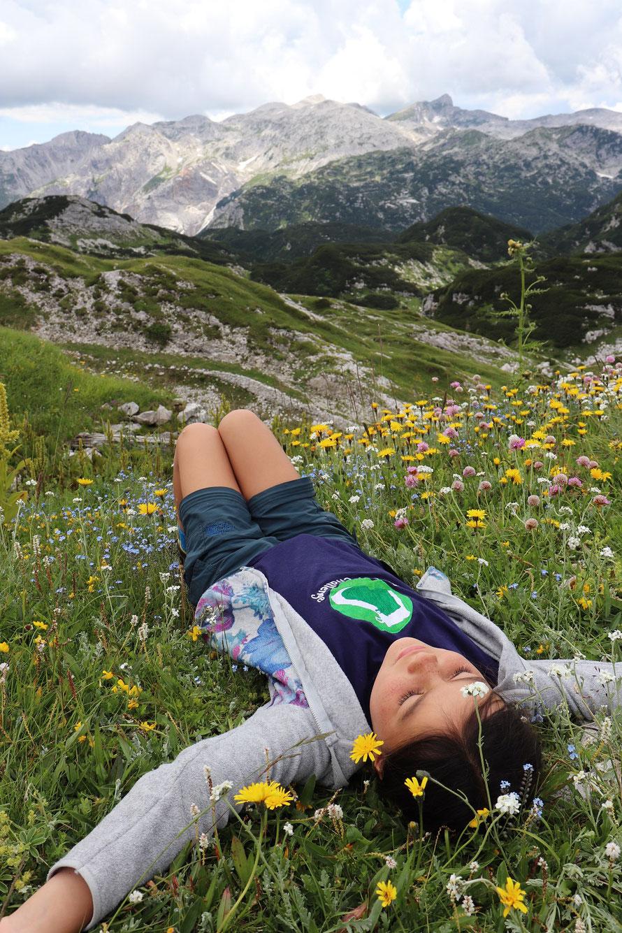 Das Foto unseres Sommers - Miriam liegt im Blumenmeer mit Sicht auf Berge, Triglav Nationalpark
