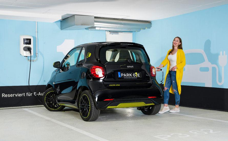 Hübsche junge Frau tankt ihr Elektrofahrzeug