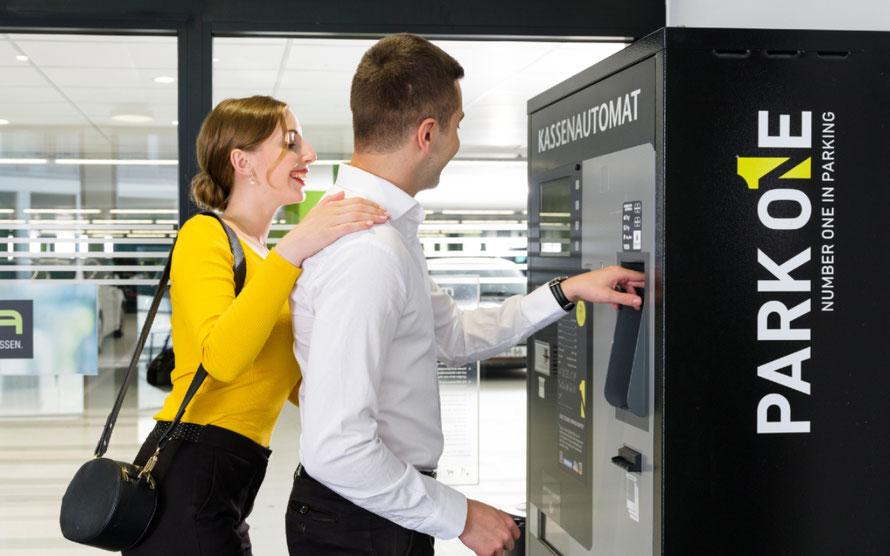 Pärchen bezahlt am Kassenautomaten ein Parkticket