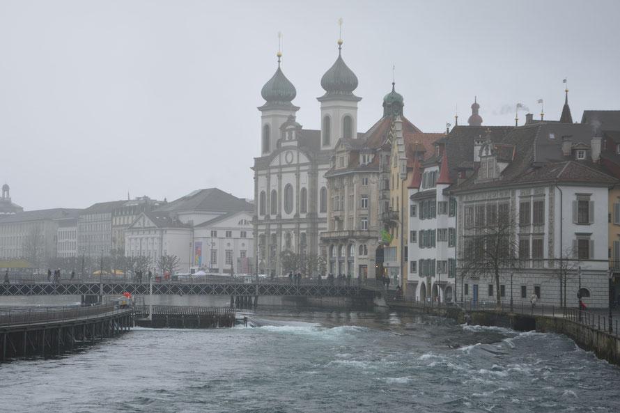 Die Jesuitenkirche, links daneben das Stadttheater. Die Reuss führt sehr viel Wasser.