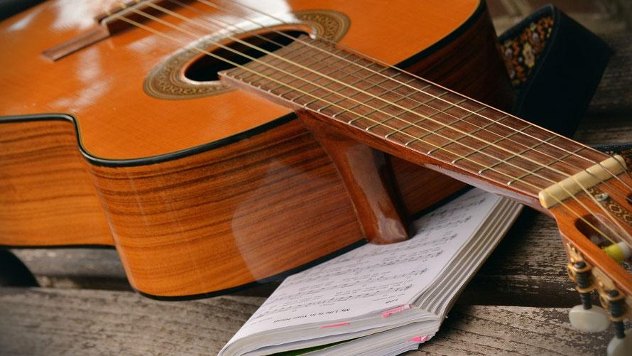 Konzertgitarre mit Notenheft auf einer Holzbank