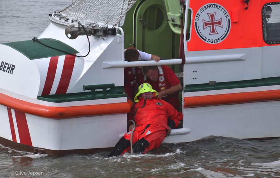 Rückwärts wird der Seemann an Bord gezogen.