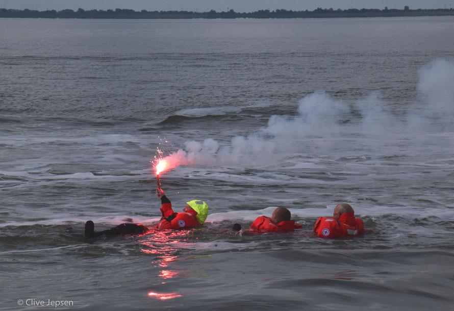 """Die schlimmste Situation eines Seefahrers. Hier haben die """"Freiwilligen"""" ihre Überlebungsanzüge an.  Vor Zündung der roten Magnesium Fackel wurden zwei Leuchtraketen abgefeuert."""