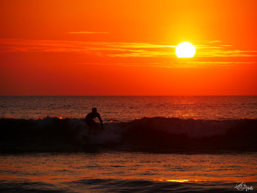 Wellenreiten im Sonnenuntergang in Ecuador