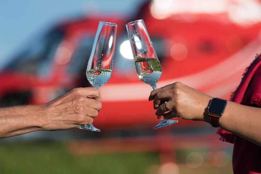 Anstossen mit den Sektgläser bei einem Helikopterflug