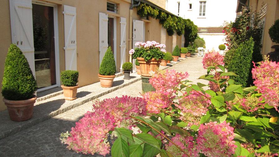 La cour privée revêtue de  pavées plantée de buis et fleurie