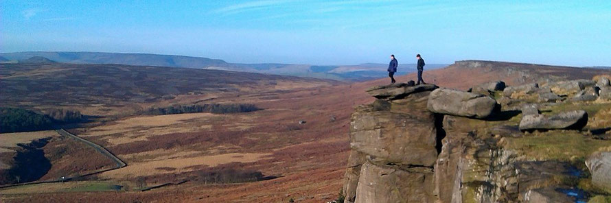 Two people standing on Stanage Edge, on a rock where actress, Keira Knightley, was filmed in the 2005 Pride and Prejudice movie