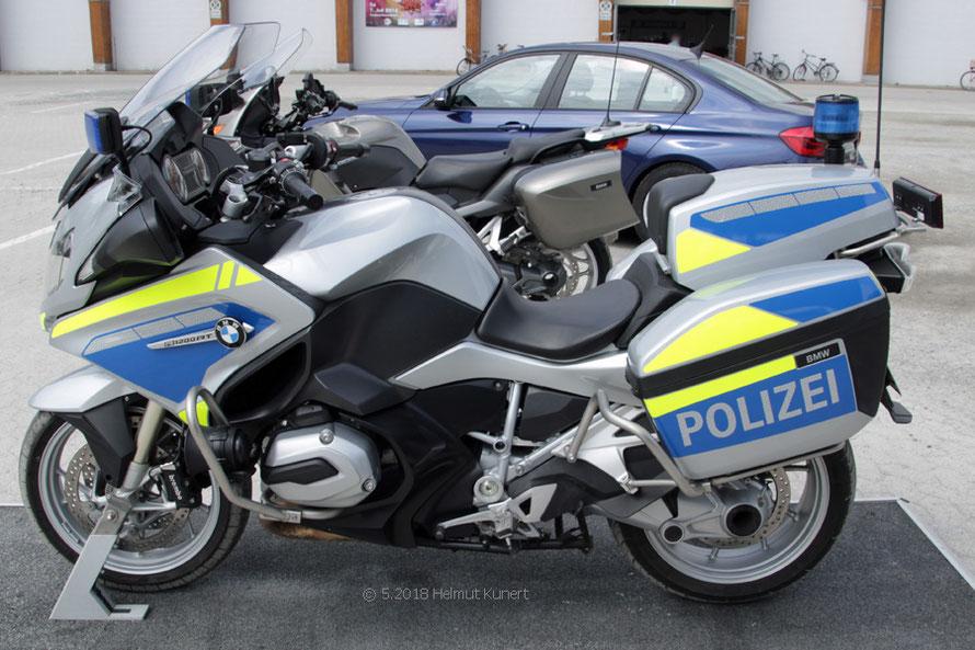 Im Hintergrund ein ziviles Polizeimotorrad zur Verkehrsüberwachung.