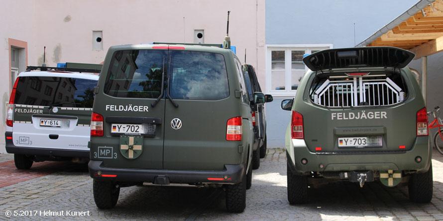 Drei olive Hundeführerfahrzeuge und ein Streifenfahrzeug.