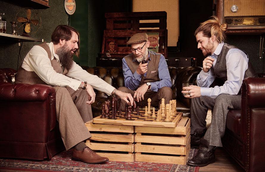 Drei Männer in Tweedanzug im Retrostil spielen Schach im Barber Shop, Kassel