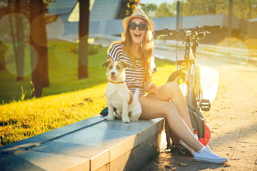 Fahrradkörbe für Hunde - Frau und Hund mit Fahrrad in der Sonne