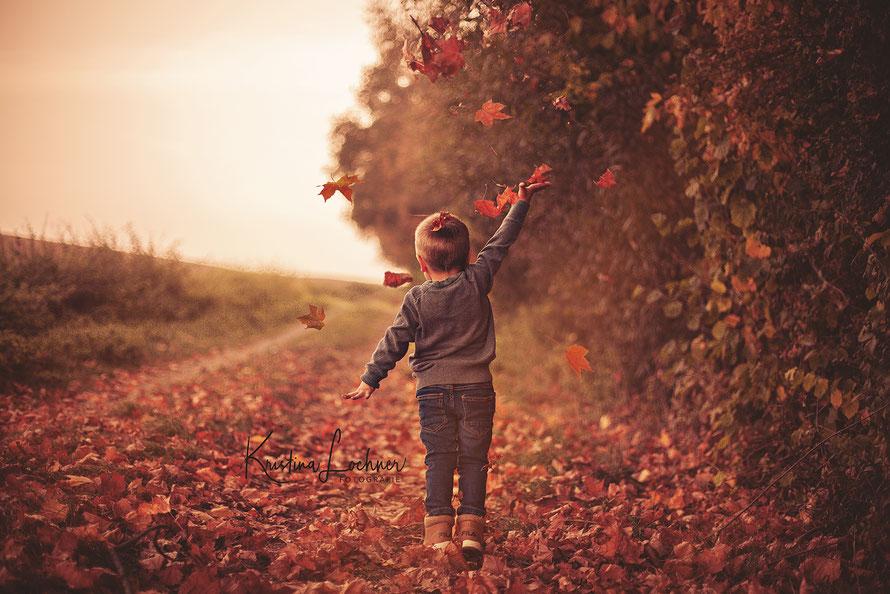 Kind im Herbst mit Laub