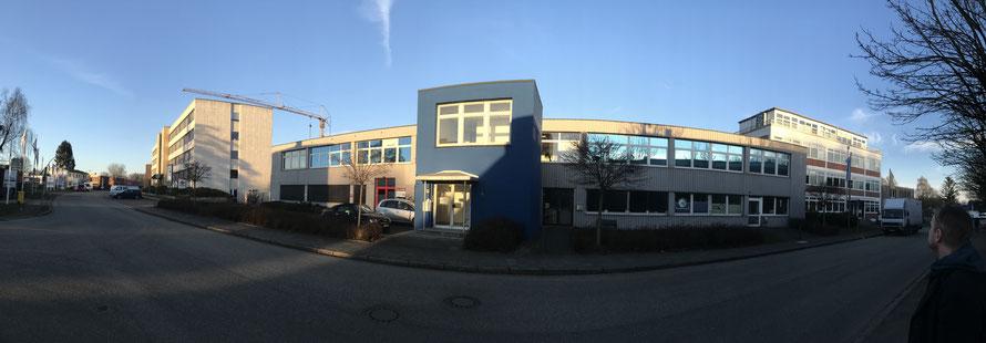 Gebäude (Aufnahme mit Fischaugenoptik) vor blauem Himmel. In der Mitte ein blauer Gebäudeteil mit Treppenhaus