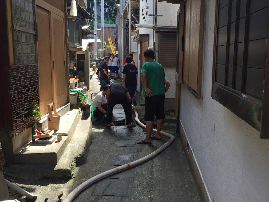消防団員と、ここの井戸を利用する家の人たちが協力して側溝の清掃中