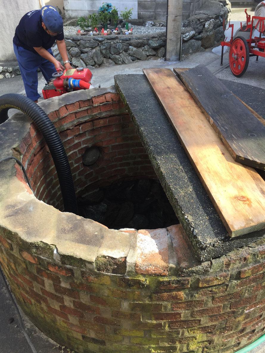 ポンプを使って井戸から水を汲み上げる様子