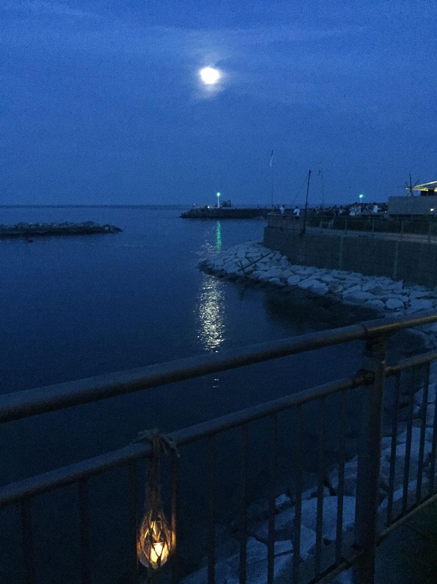月、灯台、海、堤防、音楽を楽しむ人たち。