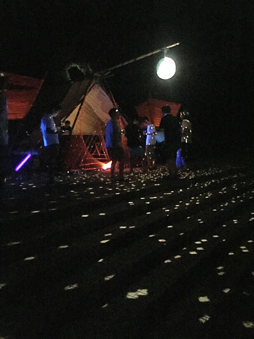 竹を組んだテントの中にDJブース。その前にはストリングを使用した飾りと、ブラックライトに照らし出される人々。ミラーボールの光が辺り一面にちりばめられています。