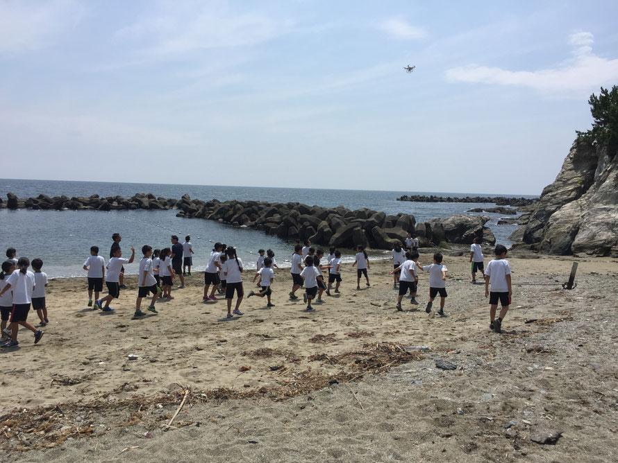 海辺でドローンを追いかける子どもたち