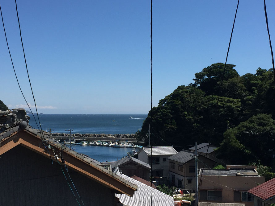 坂の上から見下ろす海、手前には家の屋根が並ぶ
